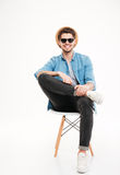 Cheerful relaxed man in hat and glasses sitting on chair Stock Images