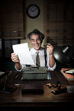 Cheerful reporter at work having a drink. 1950s style office royalty free stock photos