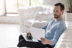Cheerful responsible man looking at the documents Royalty Free Stock Photography