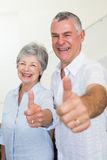 Cheerful retired couple looking at camera giving thumbs up Royalty Free Stock Image