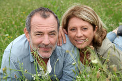 Cheerful retired couple relaxing in grass Stock Photography