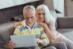 Cheerful retired couple using their laptop at home stock photo