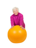 Cheerful retired lady with a pilates ball. Cheerful retired lady leaning on a bright yellow pilates ball as she uses muscle control to improve her fitness and Stock Image