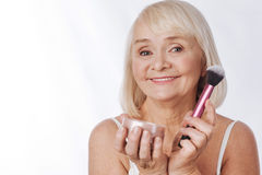 Cheerful retired woman making using face powder Royalty Free Stock Images