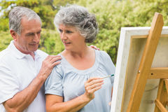 Cheerful retired woman painting on canvas and talking with husband. Cheerful retired women painting on canvas and talking with husband in the park on sunny day royalty free stock photos