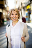 Cheerful retiree woman having a walk in city Stock Image