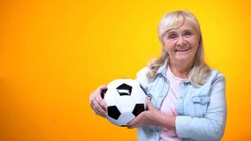Cheerful retiree woman holding football ball, sports betting, positive attitude stock photo