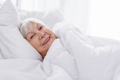 Cheerful retiree wrapping in white soft blanket Stock Images