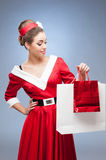 Cheerful retro girl holding shopping bags Royalty Free Stock Images