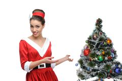Cheerful retro girl standing near christmas tree Stock Photos