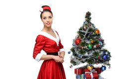 Cheerful retro girl standing near christmas tree Royalty Free Stock Image