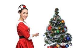 Cheerful retro girl standing near christmas tree Stock Photos