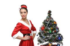 Cheerful retro girl standing near christmas tree Stock Photo