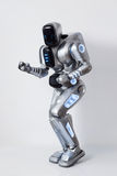 Cheerful robot dancing gin the white background. Feel the rhythm. Cheerful positive modern robot smiling and dancing while expressing gladness royalty free stock image