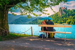 Cheerful romantic couple on the bench in the rain, Bled