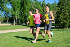 Cheerful Runners. Young cheerful people training in a park during a summer day Royalty Free Stock Photo