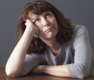 Cheerful 50s woman enjoying daydreaming Stock Photography