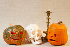 The cheerful and sad halloween pumpkin and skull. On a canvas background Stock Image