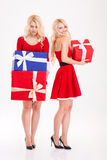 Cheerful and sad young sisters twins with present boxes Stock Photos