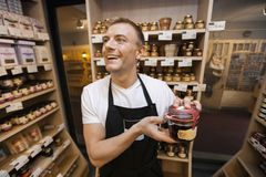 Cheerful salesman holding jar of jam in grocery store Royalty Free Stock Photos
