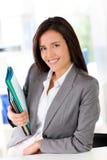 Cheerful saleswoman holding files Stock Photos