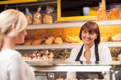 Cheerful saleswoman is serving a customer in Stock Photography
