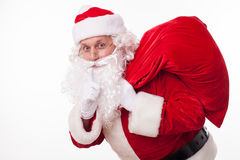 Cheerful Santa Claus is carrying presents secretly Stock Photo