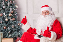 Cheerful Santa Claus is congratulating with New. Old Father Christmas is giving thumbs up with both his hands. He is sitting in his chair near a Christmas tree Royalty Free Stock Photography