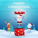 Cheerful santa claus in gift box, snowman, reindeer are christmas companion. christmas snow scene. Stock Photo