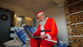 Jocund Father Christmas talking with video by laptop. Cheerful Santa Claus making video call in cozy apartments. Gladden man in red costume satisfying with stock video footage