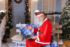 Jocund Father Christmas talking with video by laptop. Stock Images