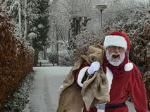 Arrival of smiling Santa Claus in a town, street of town covered. Cheerful Santa Claus with open mouth and sack of gifts arrives in town, winter park, trees in royalty free stock image