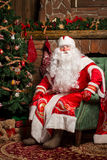 Cheerful Santa Claus sitting at his chair. With fireplace and Christmas Tree in the background Royalty Free Stock Image