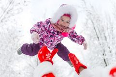 Cheerful Santa Claus throw in height baby girl in winter forest stock photography
