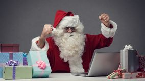 Cheerful Santa connecting with his laptop. Cheerful winner Santa connecting with his laptop at home, he is celebrating with fists raised Royalty Free Stock Photo