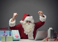 Cheerful Santa connecting with his laptop. Cheerful winner Santa connecting with his laptop at home, he is celebrating with fists raised Royalty Free Stock Image