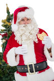 Cheerful santa eating a cookie Royalty Free Stock Image