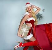 Cheerful Santa Helper girl with gift box. Royalty Free Stock Photos