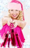Cheerful santa helper girl with shopping bags Stock Image