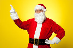 Cheerful Santa pointing away. Copy space concept. Royalty Free Stock Images