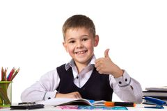 Cheerful satisfied pupil sitting at the desk with thumb up surrounded with stationery.  Royalty Free Stock Photos