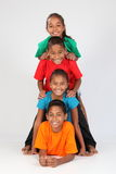 Cheerful school friends form human totem-pole. Group of four happy young ethnic school children ages 9 and 10 make a colourful human totem-pole - Canon 5D MKII Stock Photography