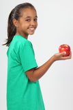 Cheerful school girl 10 smiling holding red apple Royalty Free Stock Photography