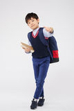 Cheerful schoolboy. Korean little schoolboy with books showing thumbs-up Royalty Free Stock Photo