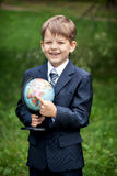 Cheerful schoolboy pointing at the globe in his hands outdoors Stock Photography