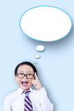 Cheerful schoolboy with speech bubble. Portrait of a smart little boy having idea and pointing at empty speech bubble Stock Photography