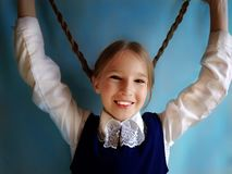Cheerful schoolgirl on a blue background stock images