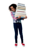 Cheerful schoolgirl carrying pile of books Royalty Free Stock Image