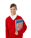 Cheerful schoolgirl holding books Royalty Free Stock Images