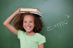 Cheerful schoolgirl holding her book on her head Stock Photography